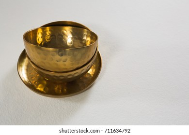 Close-up of golden steel bowls and plate on white background