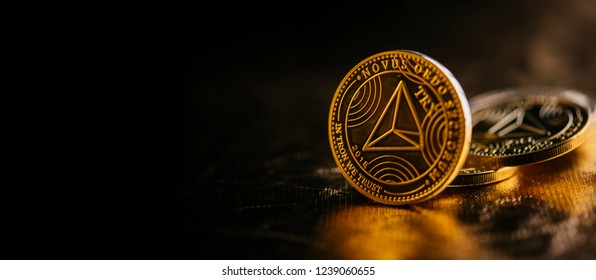 Closeup of golden tron coin TRX cryptocurrency over black and gold background. Virtual money altcoin and blockchain concept.