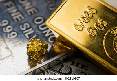 Close-up of a gold-ingot and nugget on top of a troy ounce silver and dollar banknotes