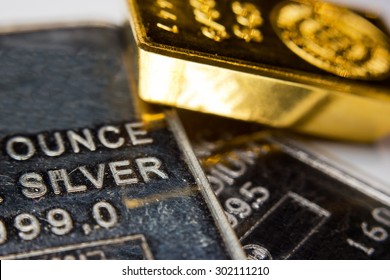 Close-up of a gold-ingot on top of a troy ounce silver and palladium bar