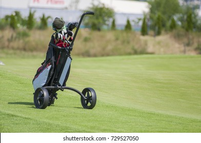 Closeup of golf trolley with clubs in golf course. Trolley on the fairway