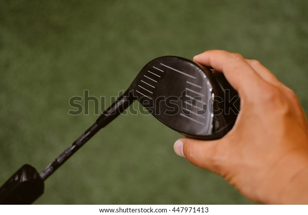 Closeup of a golfers hand using golf club, green grass background