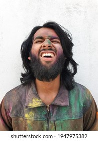 Closeup of good looking young man covered with multi color holi powder with white wall background, Bearded and long haired Indian guy celebrating Holi festival, Man making his face with eyes closed