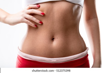 closeup of a good shaped woman's flat belly after or because of a good workout