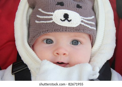 Close-up of gorgeous baby girl sitting in a pram wearing a fun winter hat
