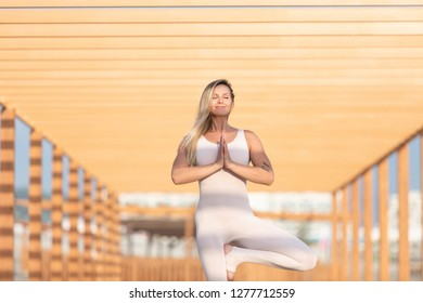 close-up Gorgeous graceful young blonde female fitness is engaged outdoors on a wooden platform in the middle of a rocky beach and makes vrikshasana on a sunny summer day