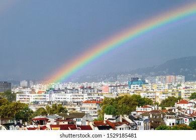 Close-up of gorgeous rainbow over residential area of the city. Scenic summer cityscape with a rainbow. Beauty in nature.