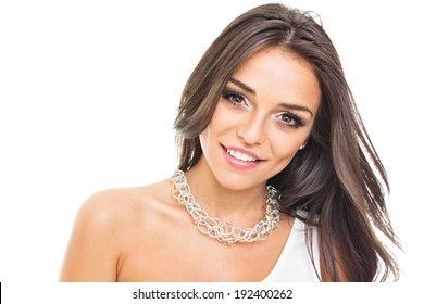 Closeup of gorgeous young mixed race woman with long hair wearing silver modern necklace smiling looking at camera isolated on white background. Beauty and fashion concept.