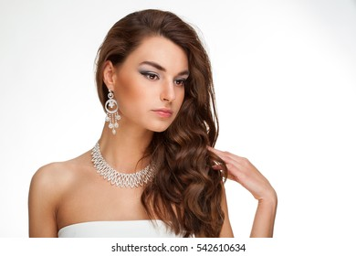 Closeup of gorgeous young mixed race woman with long hair wearing silver modern necklace looking at camera on white background. Beauty and fashion concept.