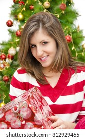 Closeup of gorgeous young woman i red sweater holding gift in her hands