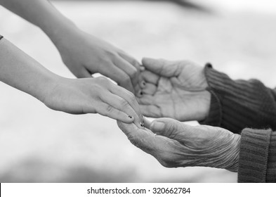 Closeup grandmother granddaughter holding hands, outdoors environment black and white edition.