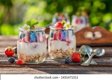 Closeup of granola in jar with yoghurt and berries