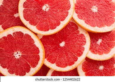 Close-up Grapefruit slices abstract background in Living Coral color of the Year 2019. Bright summer texture.