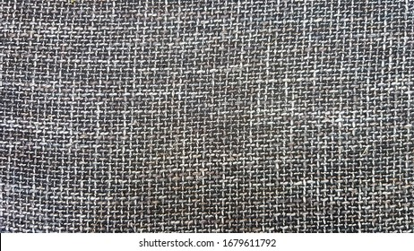 Close-up of gray fabric texture, background and wallpaper. The texture of the fabric is gray, textile upholstery. Gray tweed texture, gray wool pattern