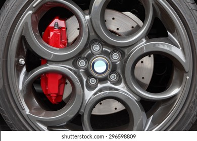 Close-up of gray, painted light weight, alloy wheel with a modern design featuring large circles. The red brake calipers stand out. Drilled disc brake. Low profile sports car tires. Alfa Romeo 4c.
