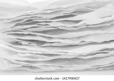 Closeup of gray paper layers stack. Wavy lines abstract art background. Copy space.