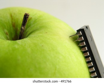 Close-up of green apple with chip attached as a symbol for bio-genetical manipulations