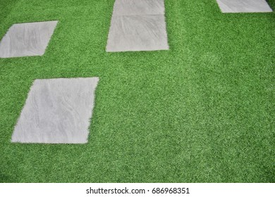 Closeup green artificial grasses field and cement path