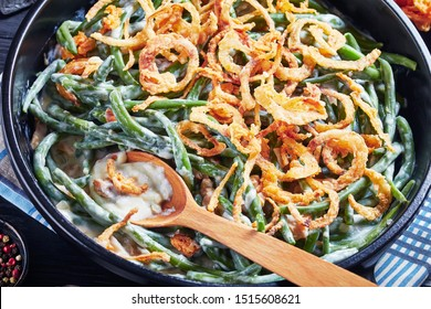close-up of Green Bean Casserole topped with crispy fried onions in a black dish with spoon,  american cuisine, view from above