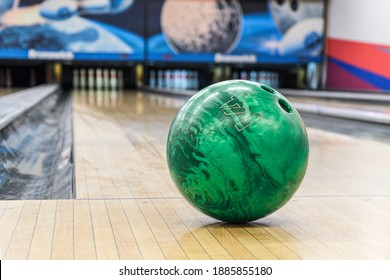 Close-up of green bowling ball against background of empty lanes in bowling alley. Active leisure. Sports activities for whole family. Space for text. Selective focus, blurred background