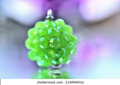 Close-up of green earring jewelery - reflection effect - colored backgrounds