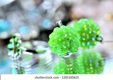 Close-up of green earrings jewelery - reflection effect - colored backgrounds