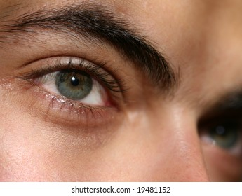 Closeup of green eyes of young man with a serious look on his face