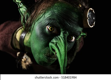 closeup, green female goblin with a long nose and freaky ears, Halloween or carnival theme