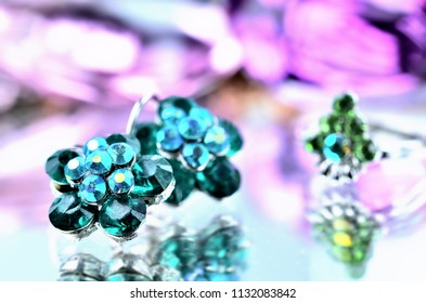 Close-up of green flower shaped earrings with geeen diamonds jewelery - reflection effect - ring in backgrounds