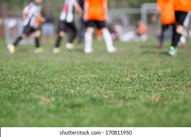 Close-up of green grass at football (soccer) pitch with blurred players in the background.