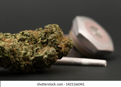 Closeup of green marijuana bud with rolled joint and metallic grinder as drug concept isolated on black background