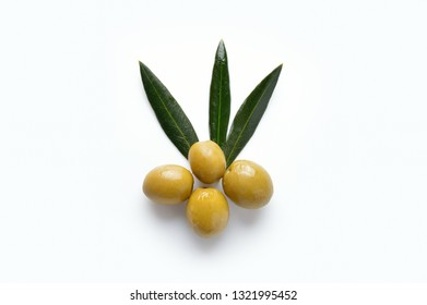 Closeup of green olives with olive branch on white background