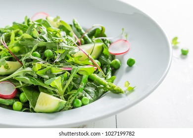 Closeup of green salad with spinach, radishes and asparagus