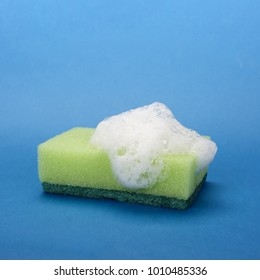 Close-up of a green soapy sponge on blue background