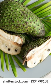 Closeup of green soursop graviola, exotic, tropical fruit Guanabana on plate decorated palm leaves. Alternative medicine treatment of cancer