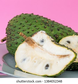 Closeup of green soursop graviola, exotic, tropical fruit Guanabana on pink background. Alternative medicine treatment of cancer