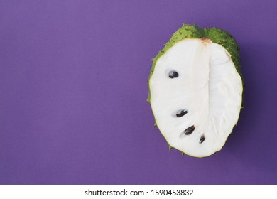 Closeup of green soursop graviola, exotic, tropical fruit Guanabana on purple background. Place for text.