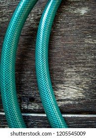 closeup green water hose on plank floor