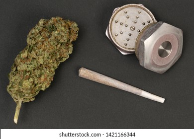 Closeup of green weed bud rolled joint and metallic grinder isolated on black studio background