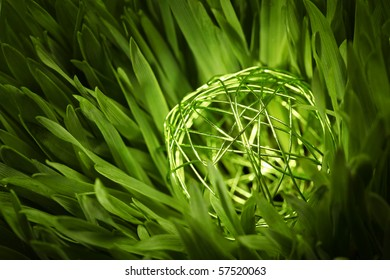 close-up of a green wire orb in green grass