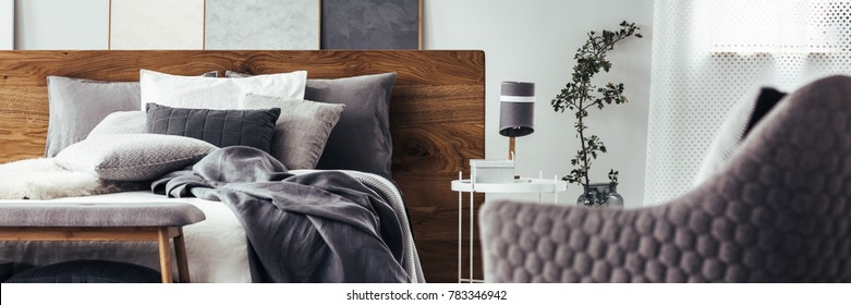 Close-up of grey blanket and cushions on bed with wooden bedhead in bedroom interior with lamp, plant and armchair