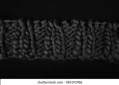 Closeup of grey chunky wool on black fabric surface.  Knit and purl knitting stitches. Copy space in upper and lower part of image horizontal.