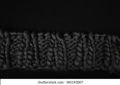 Closeup of grey chunky wool on black fabric surface.  Knit and purl knitting stitches. Copy space in upper part of image.