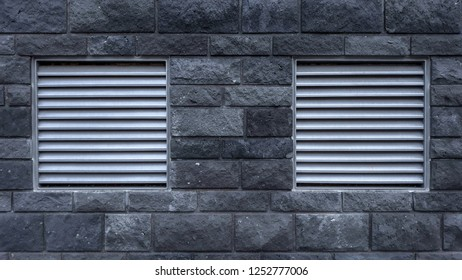 Close-up of a grey Stone Wall with silver colored square Shutters.