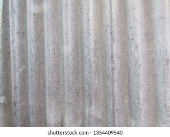 Closeup of grey waved asbestos roof tile texture wallpaper. Asbestos cement roofing sheets, corrugated panels background fiber cement and siding standard