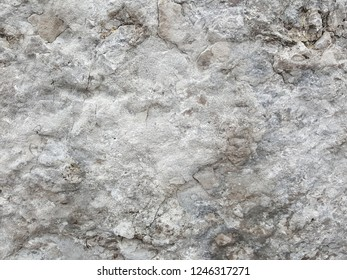 Closeup of grey, weathered stone texture background with cracks and markings.