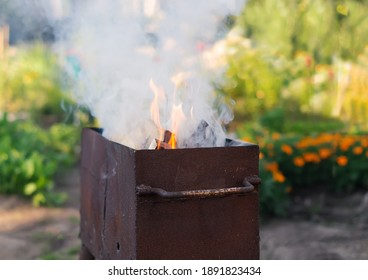 Close-up of a grill with a large flame and smoke outside in the backyard on the lawn. We build a fire in a homemade barbecue for cooking shish kebab. The concept of family, tourist holidays