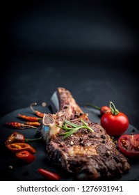 Close-up of grilled beef steak on bone with tomatoes on the stone cutting board with copy space