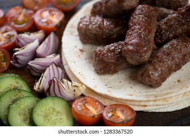Closeup of grilled cevapcici or skinless beef sausages on tortillas with vegetables, selective focus