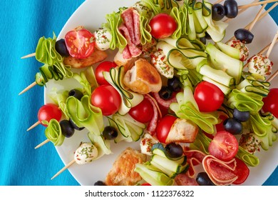 close-up of grilled chicken meat shish kebab skewers with raw zucchini ribbons, tomatoes, mozzarella balls, salami slices, black olives on a white plate, view from above, flatlay